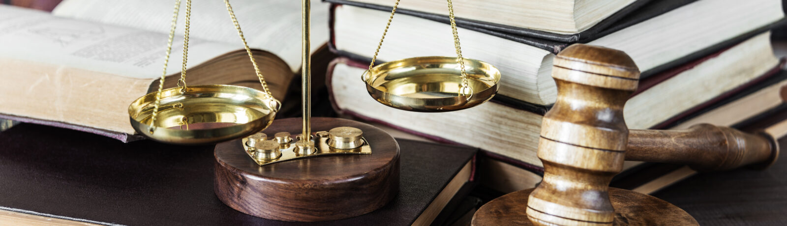 Scales and gavel against background of books.