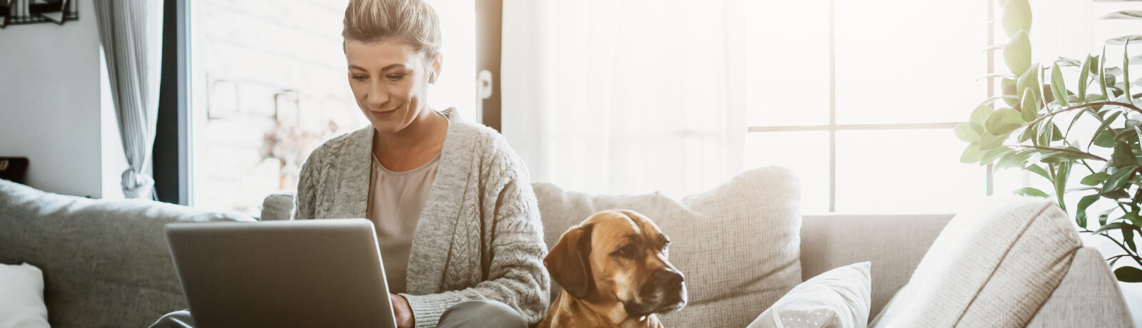 Middle-aged woman working from home next to her pet dog.