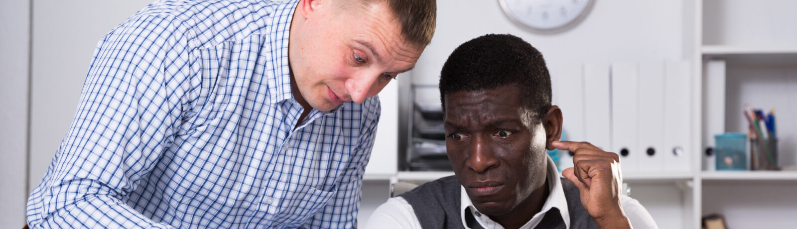 Employee looking worried as his coworker shows him something on a piece of paper.