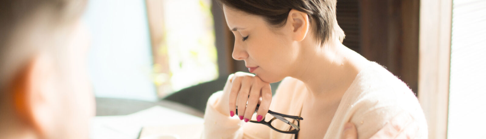 Exhausted adult woman holding glasses and keeping eyes closed while sitting near colleague at cafe table.