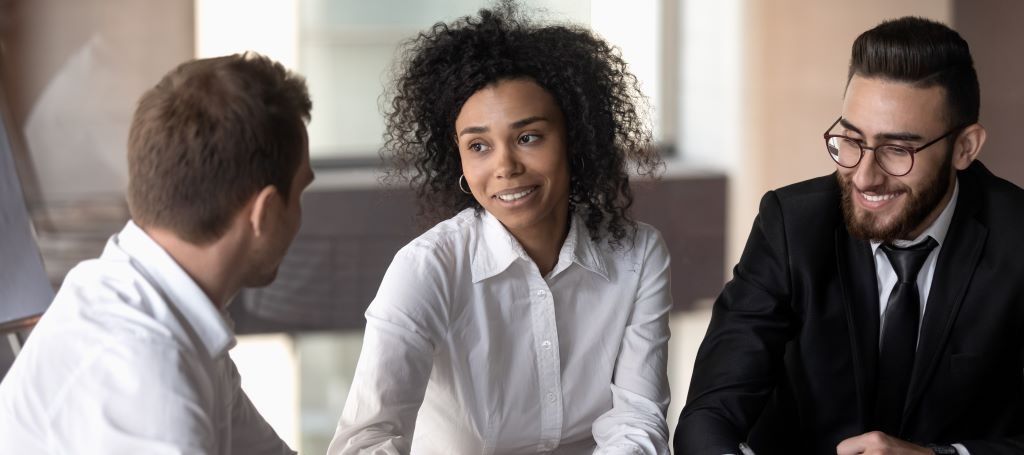 Black businesswoman speaks intently to two male colleagues