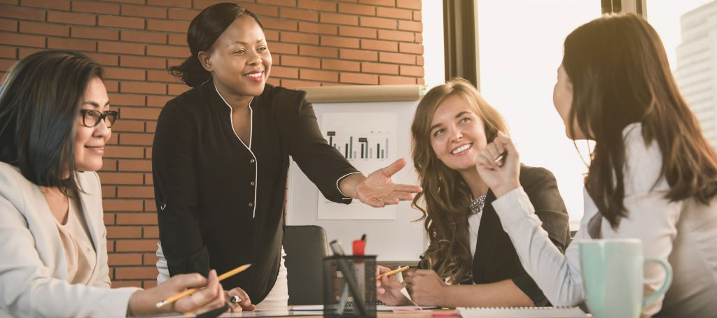 Black businesswoman leads meeting with three women employees