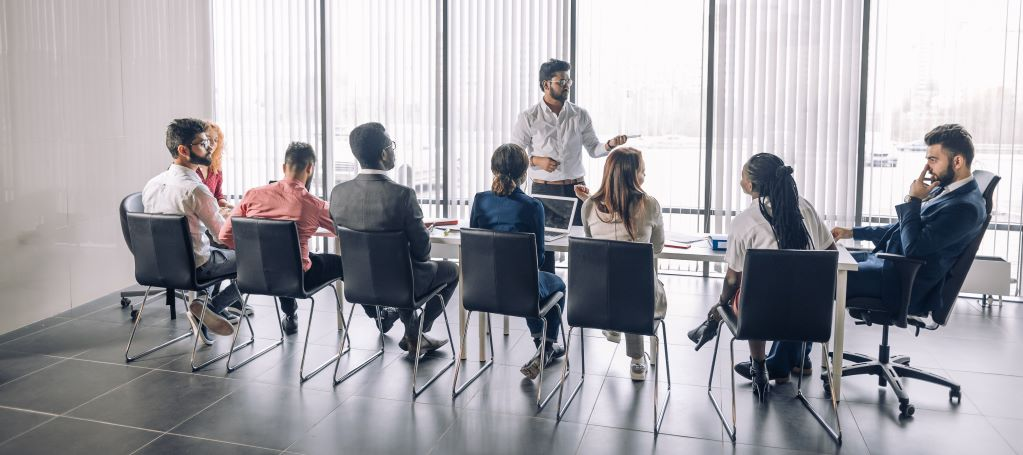 Businessman stands at conference table while talking to team