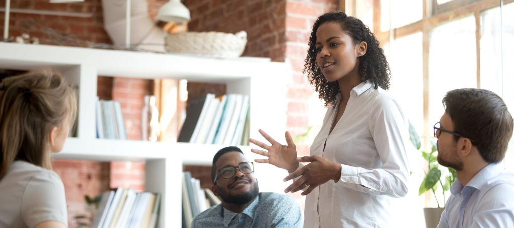 Black Businesswoman stands and presents idea at a meeting