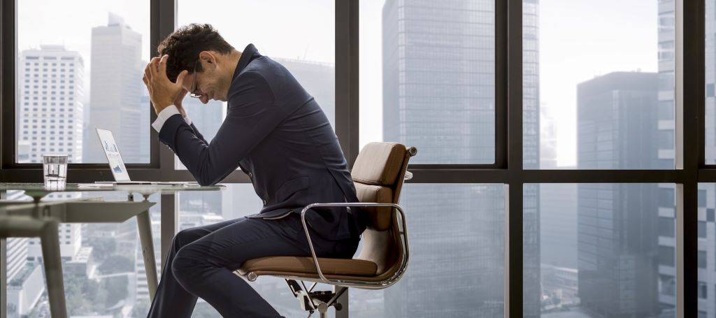 Business man sits at end of conference table with his head in his hands