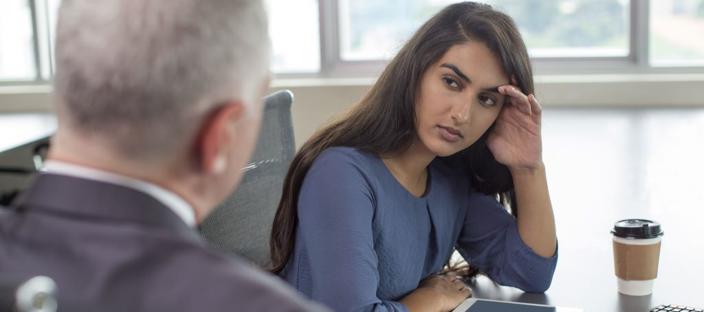 Young South Asian business woman leans on hand and looks seriously at businessman who is talking to her.